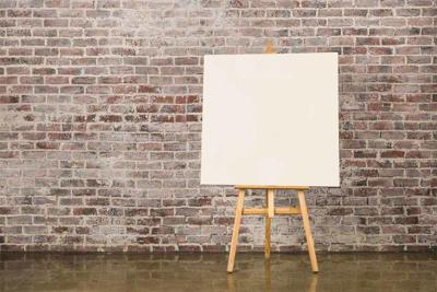 41895762 - easel with blank canvas on a brick wall background