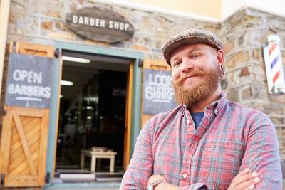 Portrait Of Hipster Barber Standing Outside Shop