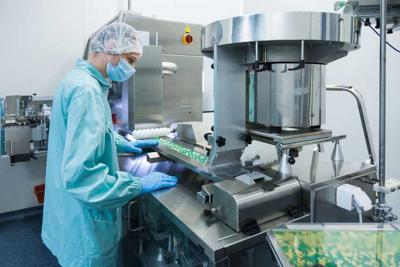Pharmaceutical industry man worker in protective clothing operating production of tablets in sterile working conditions