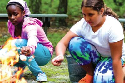 Girl Scouts toasting marshmallows