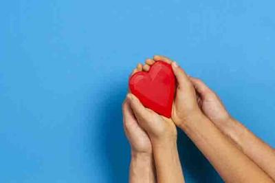 Adult and child hands holding red heart over blue background. Love, healthcare, family, insurance, donation concept
