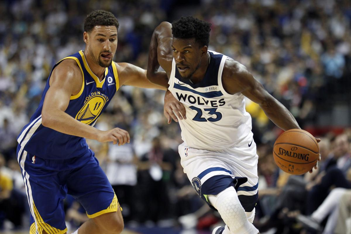 3bee3b6e595c China NBA. Minnesota Timberwolves  Jimmy Butler (23) drives past Golden  State Warriors guard Klay Thompson during a preseason game in Shanghai ...