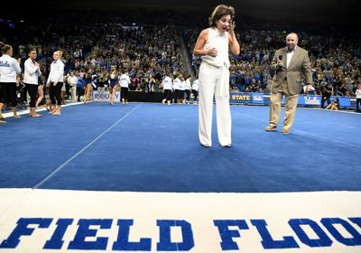 UCLA head gymnastics coach Valorie Kondos Field reacts as athletic director Dan Guerrero presents her with the naming of the floor during a retirement ceremony at Pauley Pavilion on March 23, 2019 in Los Angeles.