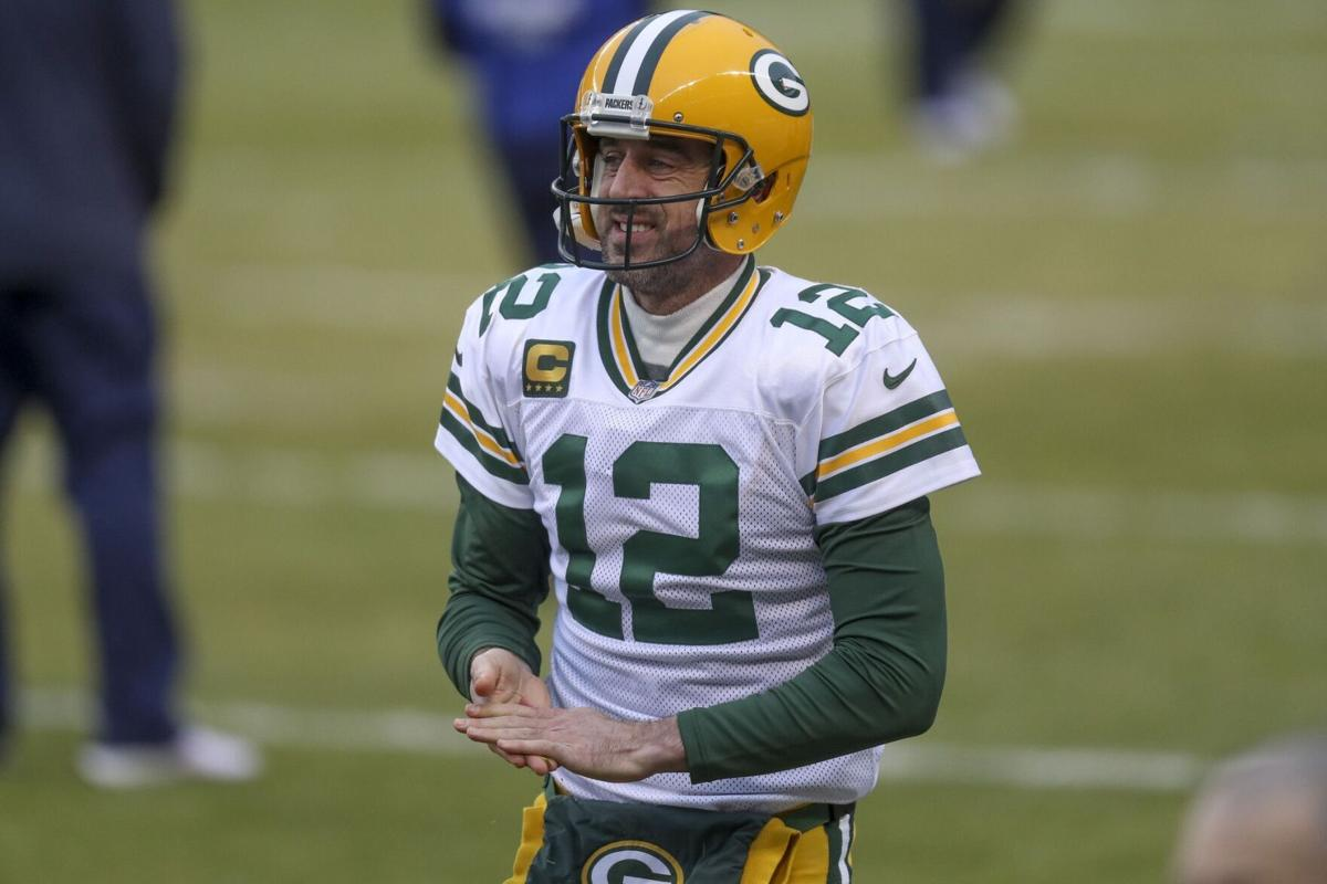 Packers quarterback Aaron Rodgers rubs grass on his hands while warming up.