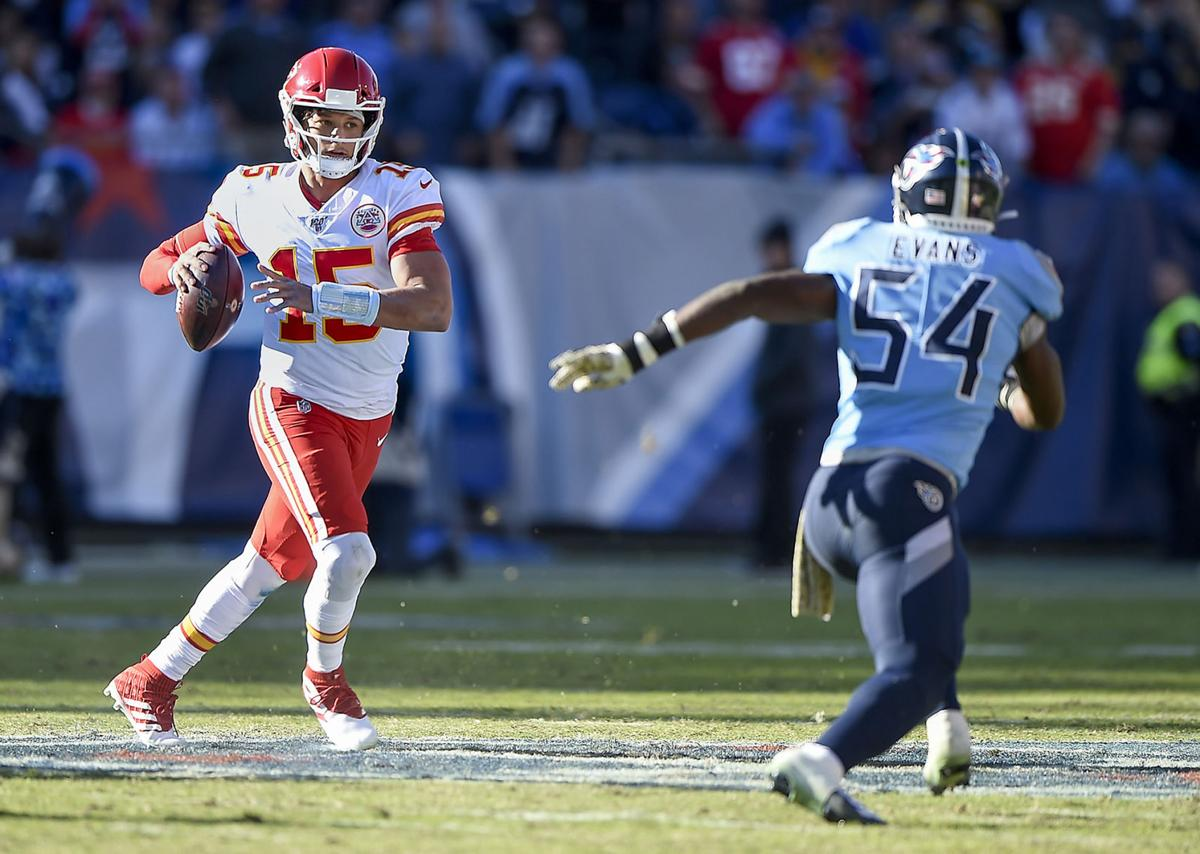Kansas City Chiefs quarterback Patrick Mahomes (15) scrambles from Tennessee Titans inside linebacker Rashaan Evans (54) before getting a pass off on Sunday, Nov. 10, 2019, at Nissan Stadium in Nashville, Tenn.