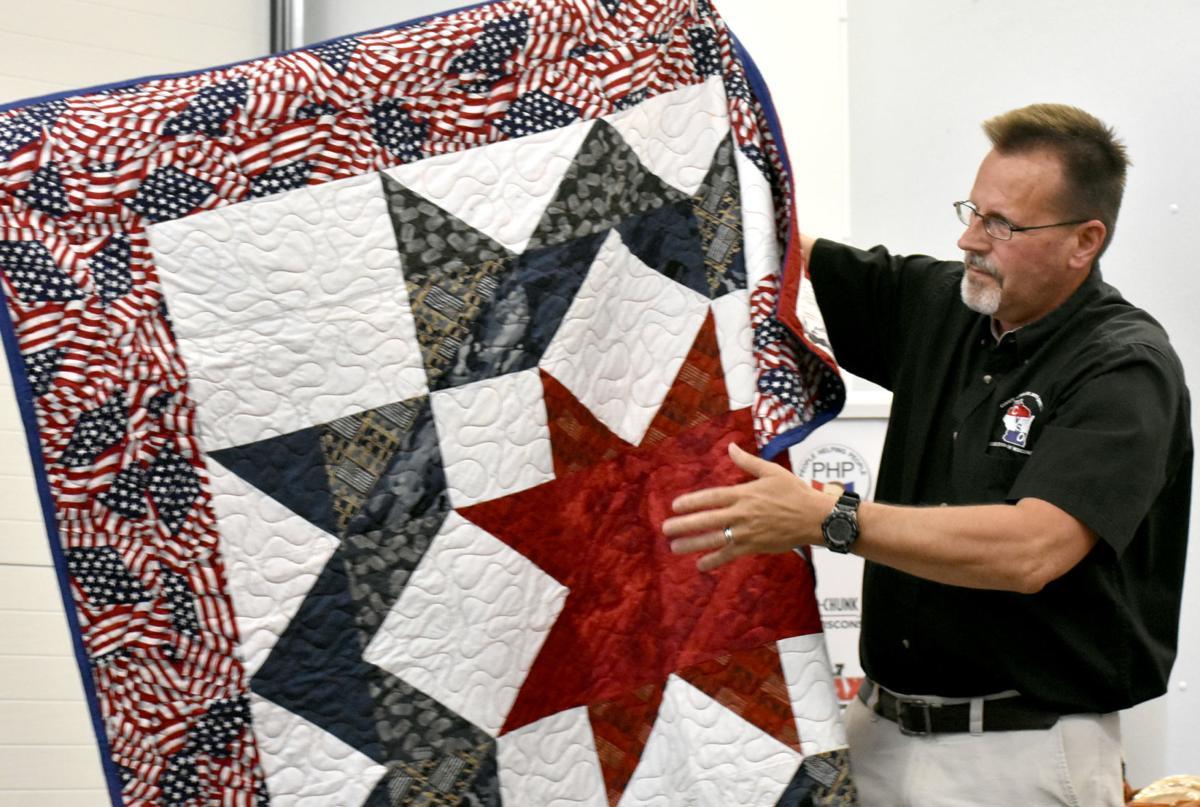 Tony Tyczynski unfolds a quilt of honor