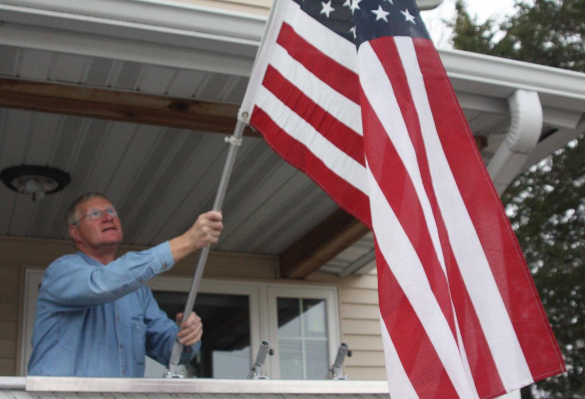 Howard Marklein puts up American flag picture