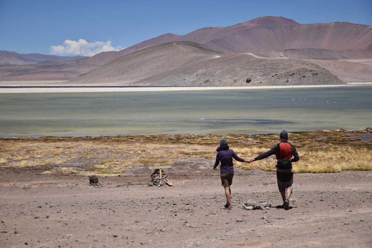 A couple walks towards the shore of Laguna Verde in Nevado Tres Cruces National Park.