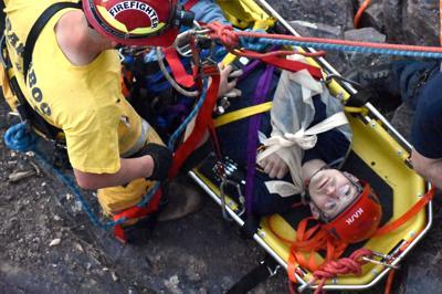 Dave Schrofer helps person on cliffs during training