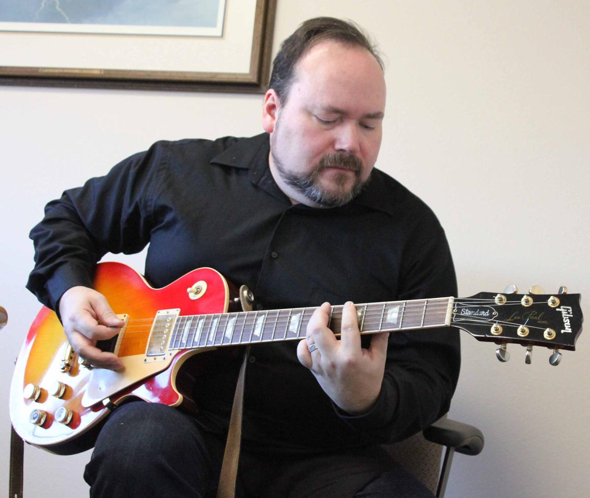 Alex Porter sitting down play guitar 2