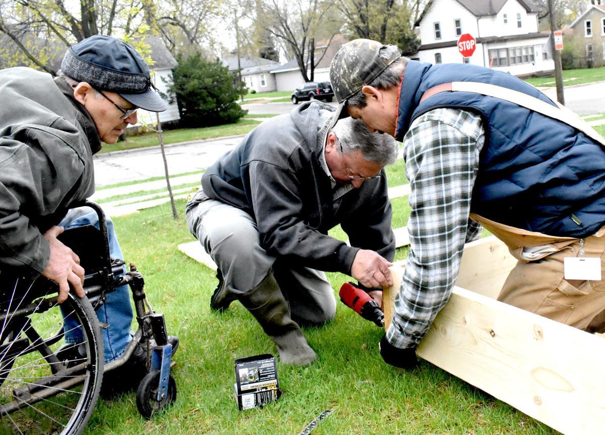 Gentlemen build raised garden bed together in Portage