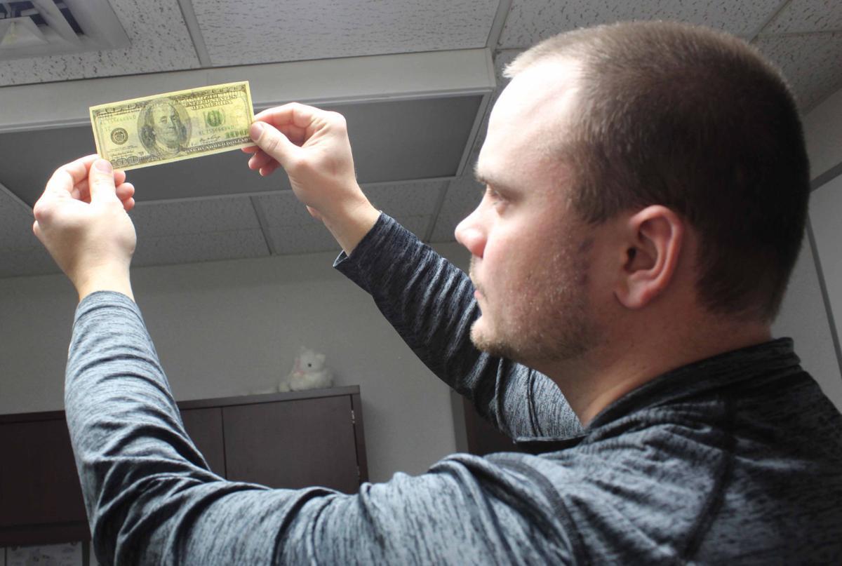 Andrew shows counterfeit money