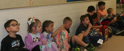 Kids sit in the hallway outside classroom