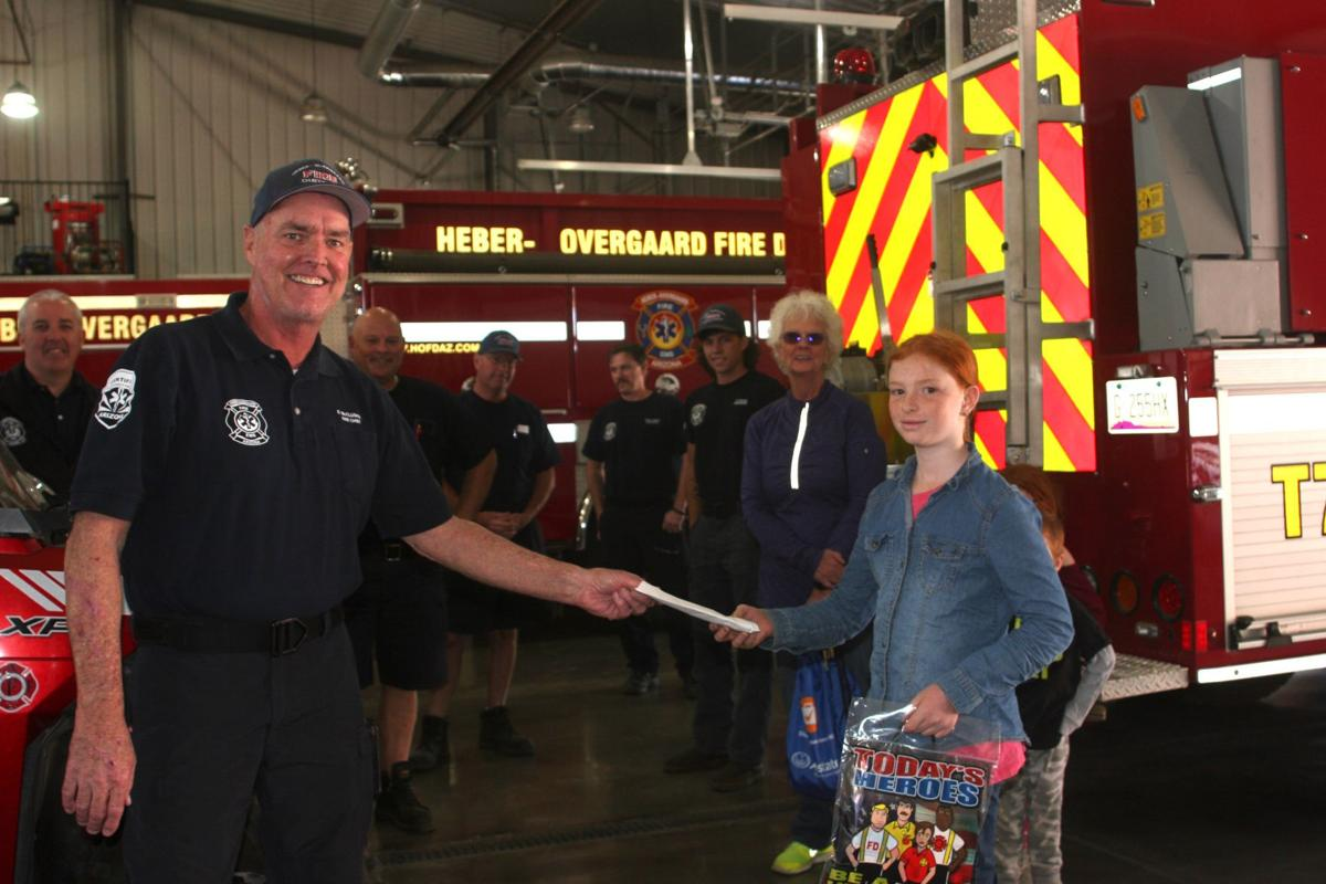 Lemonade-makin' kids donate $100 to local fire dist. - Accalia hands money over