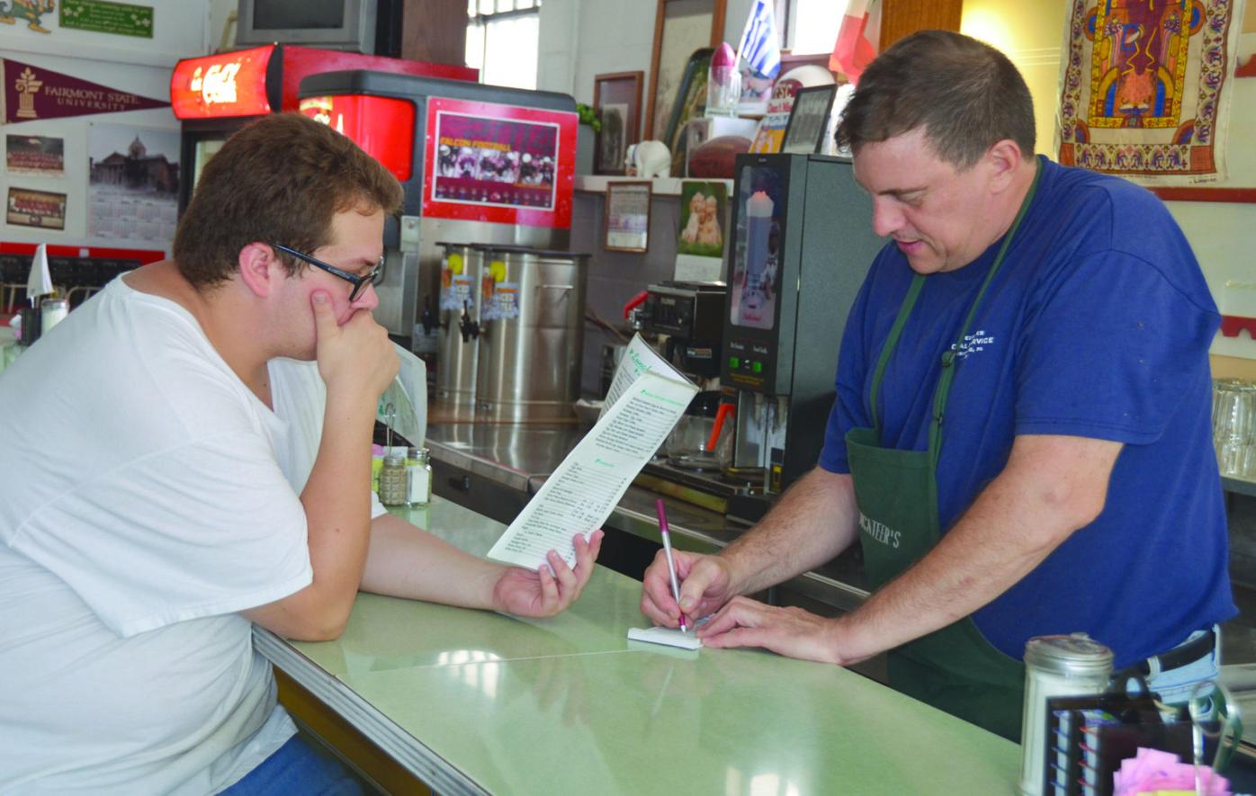 Tim McAteer, right, the owner of McAteer's in Fairmont, takes an order from Chip Tagg Wednesday. The business has been a place for locals to hang out since it opened its doors in 1958.