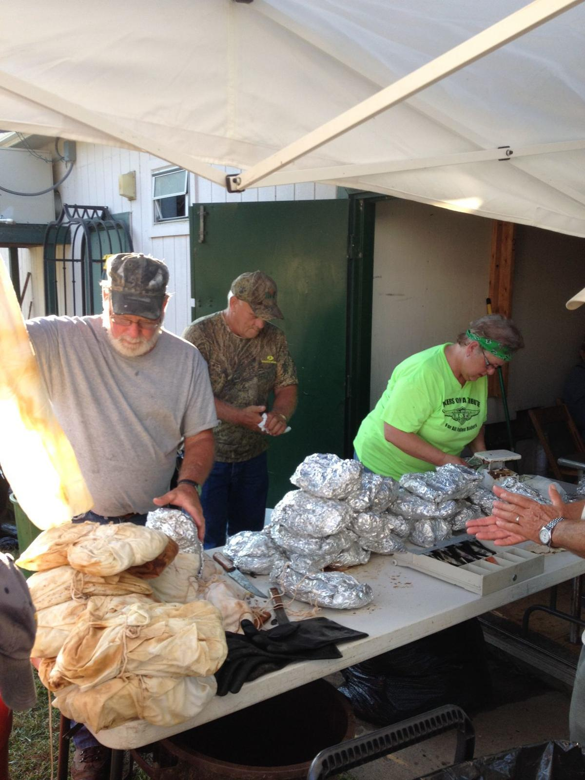 Volunteers help wrap the meat for cooking