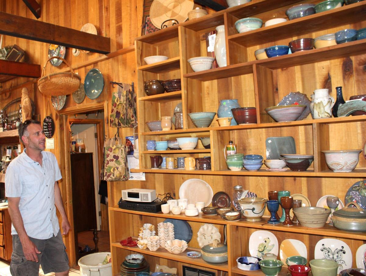 JB Lambert looks at the collection of pottery made by his mother, Debbie  Lambert, that's for sale at Lambert's Vintage Wines.