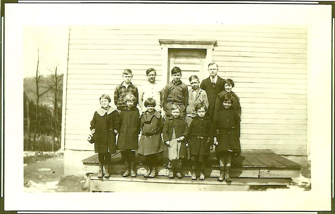 Students in front of schoolhouse