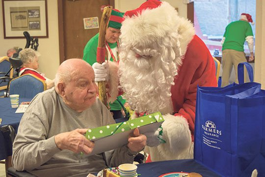 santa helps to deliver gifts last saturday at the nisqually valley nursing home