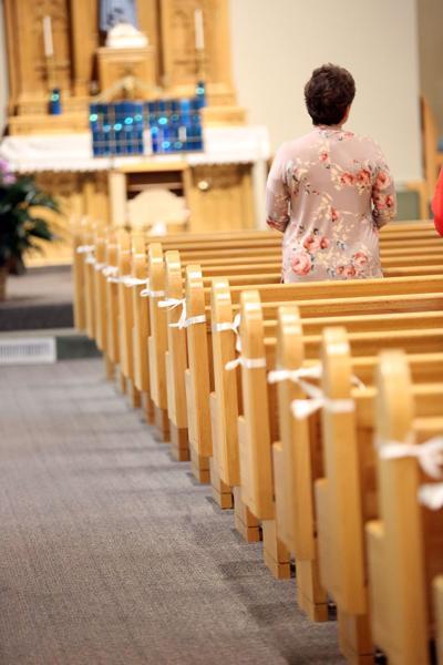 White ribbon cordons off alternating pews at St. Joseph Catholic Church