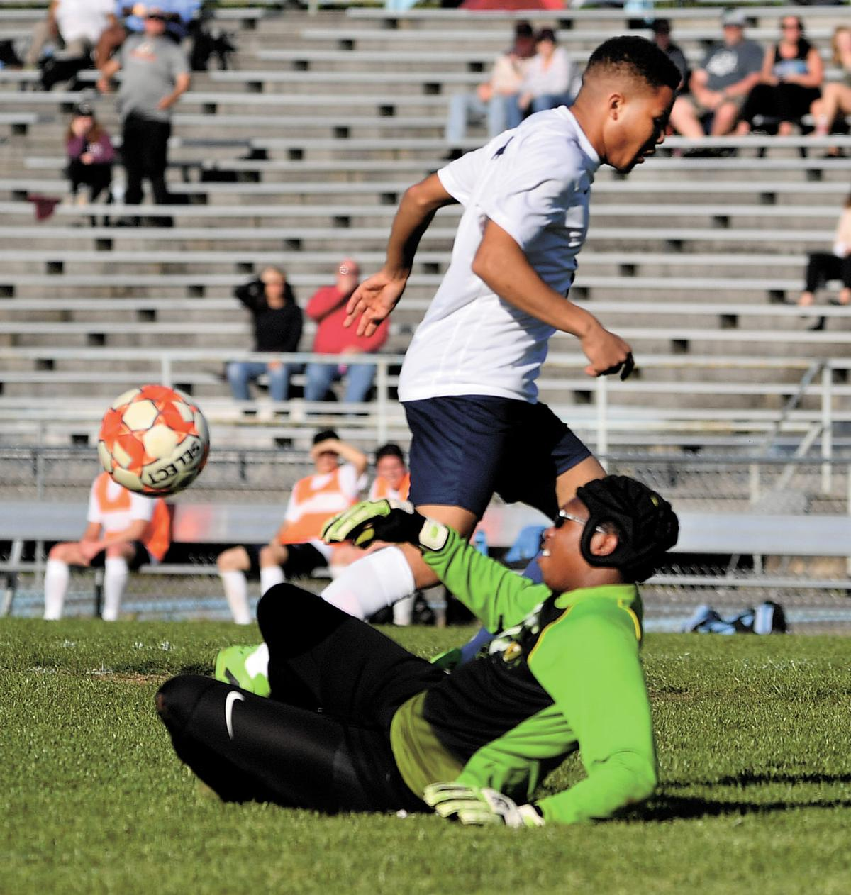 7b3094f06 Halifax County High School goalkeeper Ky Juan Walker slides to the ground  to stop a shot from an Appomattox County High School player during Monday  night s ...