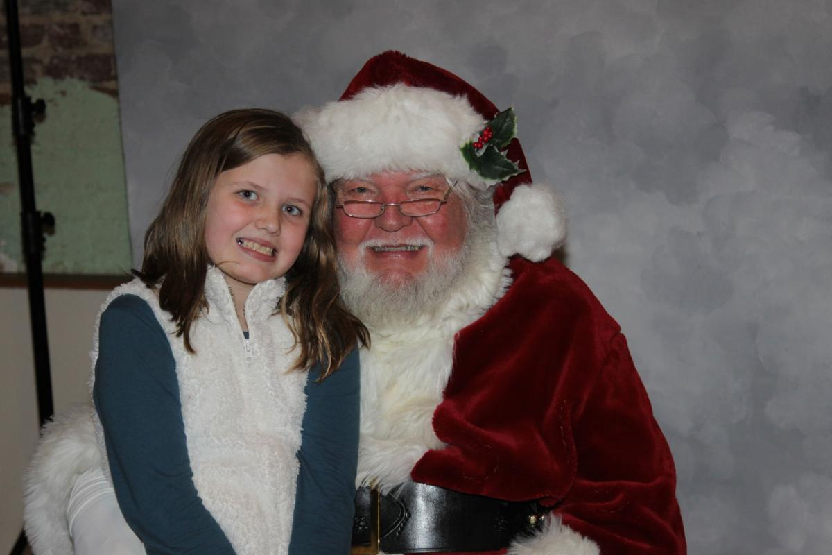 Kaylee Barksdale pays a visit to Santa Claus during Downtown South Boston s  31st annual Christmas open house on Sunday. She is the daughter of Matthew  ... e68419f53